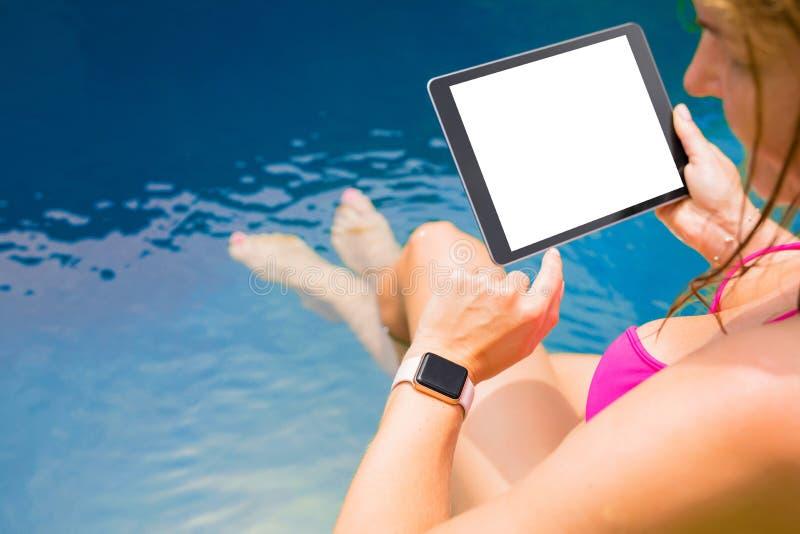 Donna che per mezzo del computer della compressa e dello smartwatch fotografie stock