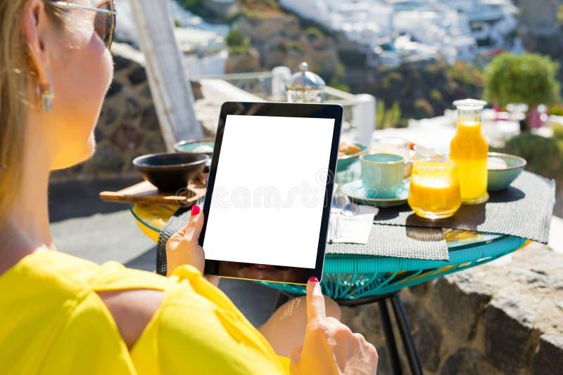 Donna che per mezzo del computer della compressa mentre mangiando prima colazione, fotografie stock libere da diritti