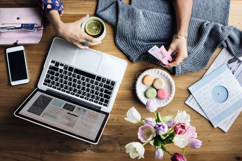 Donna che per mezzo del computer portatile che compera online fotografia stock