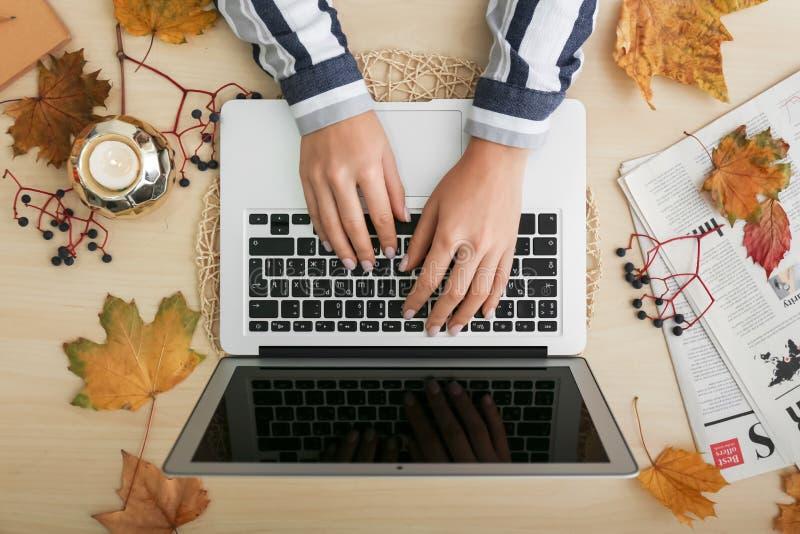 Donna che per mezzo del computer portatile sulla tavola immagini stock