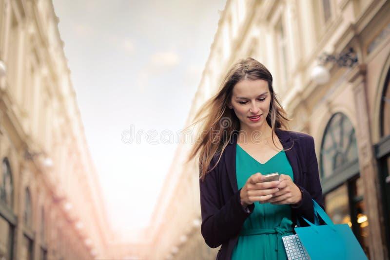 Donna che per mezzo del suo telefono fotografie stock