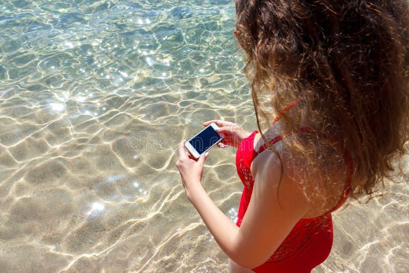 Donna che per mezzo del suo telefono cellulare sui precedenti del mare immagini stock