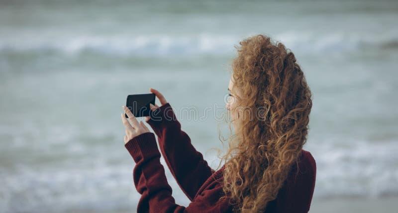 Donna che per mezzo del telefono cellulare alla spiaggia immagine stock