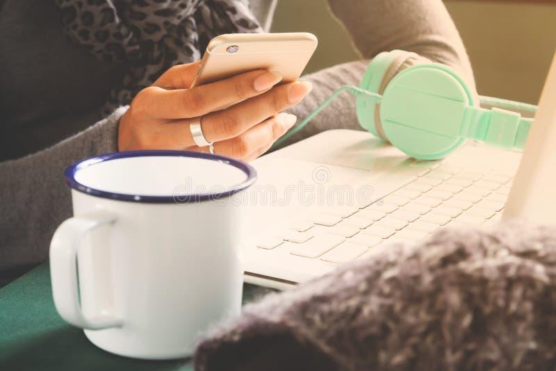 Donna che per mezzo del telefono cellulare e del computer portatile sullo scrittorio dell'area di lavoro Technolog immagine stock libera da diritti