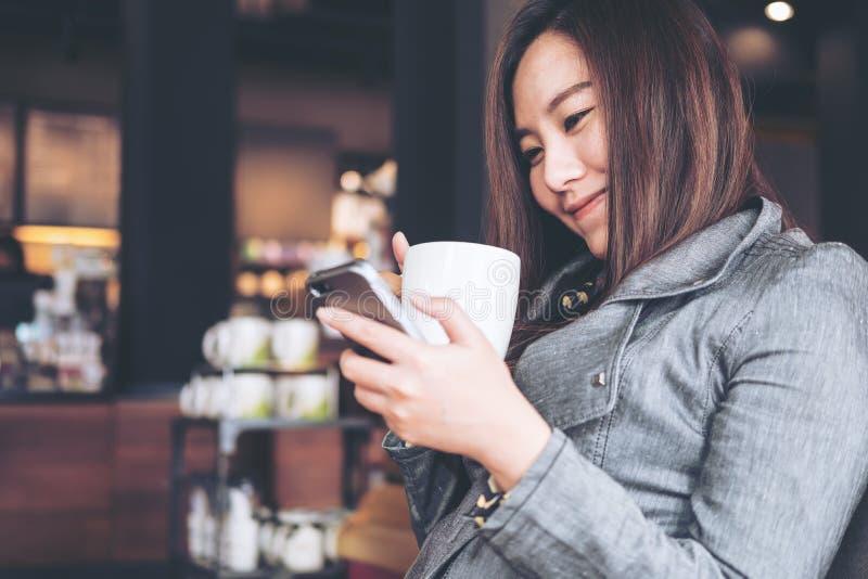 Donna che per mezzo del telefono con caffè caldo immagine stock