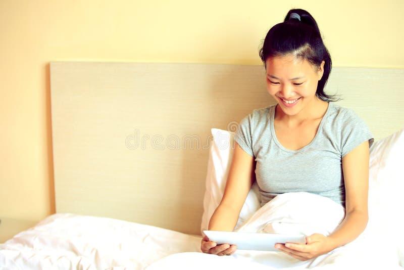 donna che per mezzo della compressa digitale a letto a casa immagini stock
