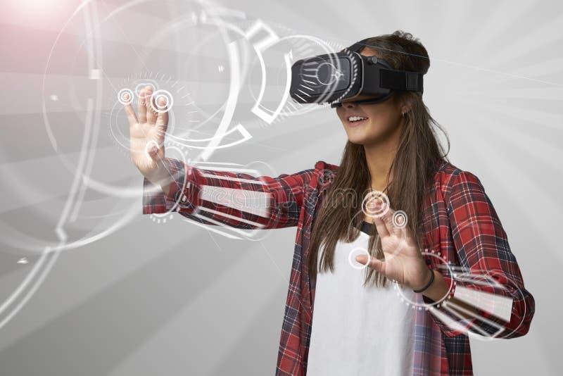 Donna che per mezzo della cuffia avricolare di realtà virtuale fotografia stock