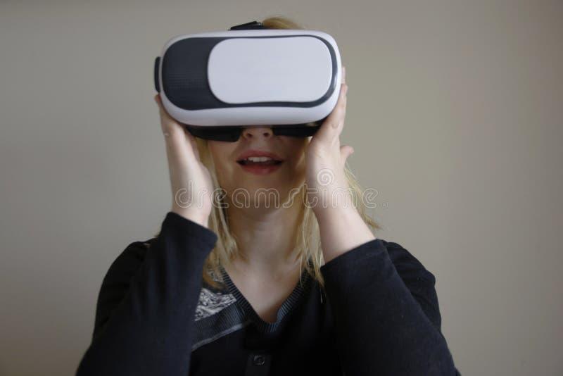 Donna che per mezzo della cuffia avricolare di VR fotografia stock