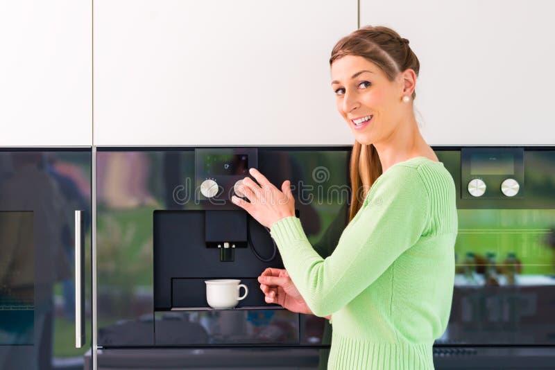 Donna che per mezzo della macchina completamente automatica del caffè fotografia stock libera da diritti