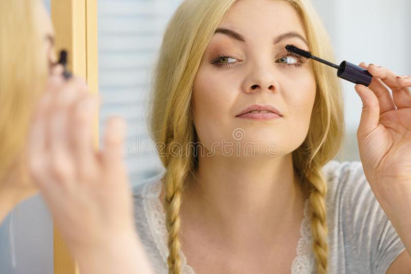 Donna che per mezzo della mascara sui suoi cigli fotografia stock