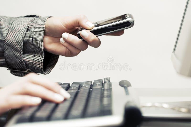 Donna che per mezzo della tastiera di computer e rivolgendo al telefono cellulare fotografia stock libera da diritti