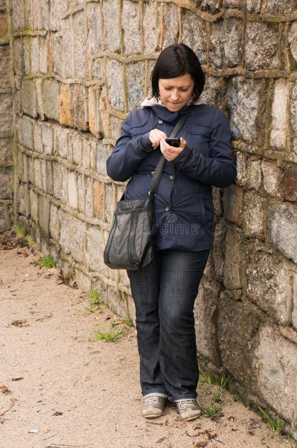 Download Donna Che Per Mezzo Dello Smartphone Immagine Stock - Immagine di brunette, messaging: 30825173