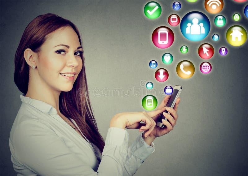 Donna che per mezzo dello smartphone con le icone dell'applicazione sociali di media che volano fuori immagine stock libera da diritti