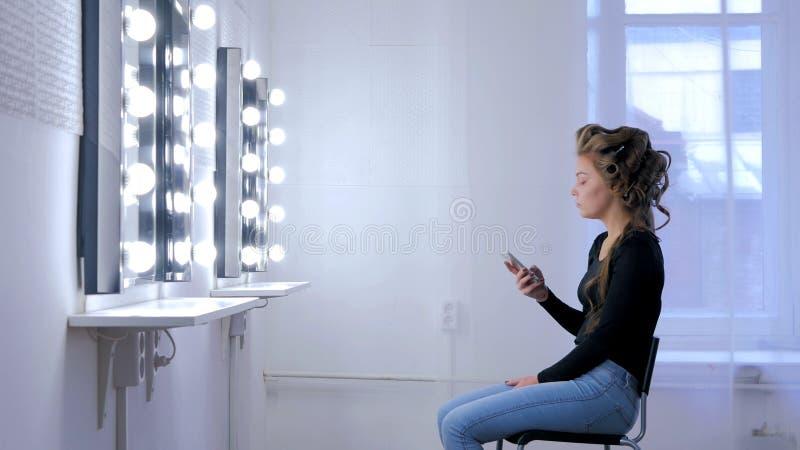 Donna che per mezzo dello smartphone che si siede davanti allo specchio immagini stock
