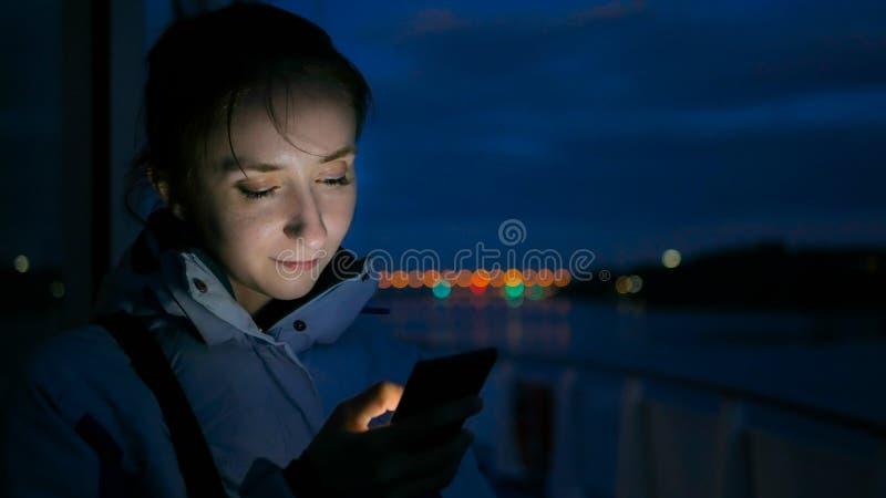 Donna che per mezzo dello smartphone verticale sulla piattaforma della nave da crociera alla notte fotografia stock