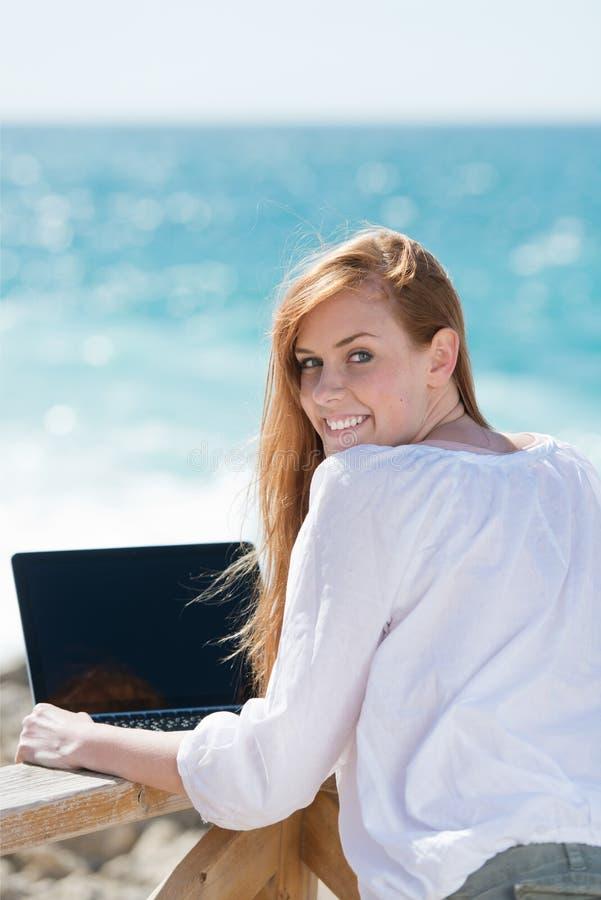 Donna che per mezzo di un computer portatile al mare fotografia stock