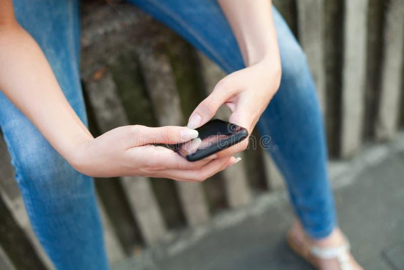 Donna che per mezzo di uno smartphone all'aperto immagine stock libera da diritti