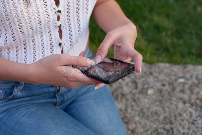 Donna che per mezzo di uno smartphone all'aperto fotografia stock
