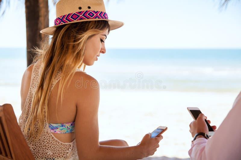 Donna che per mezzo di uno smartphone sulla vacanza immagini stock libere da diritti