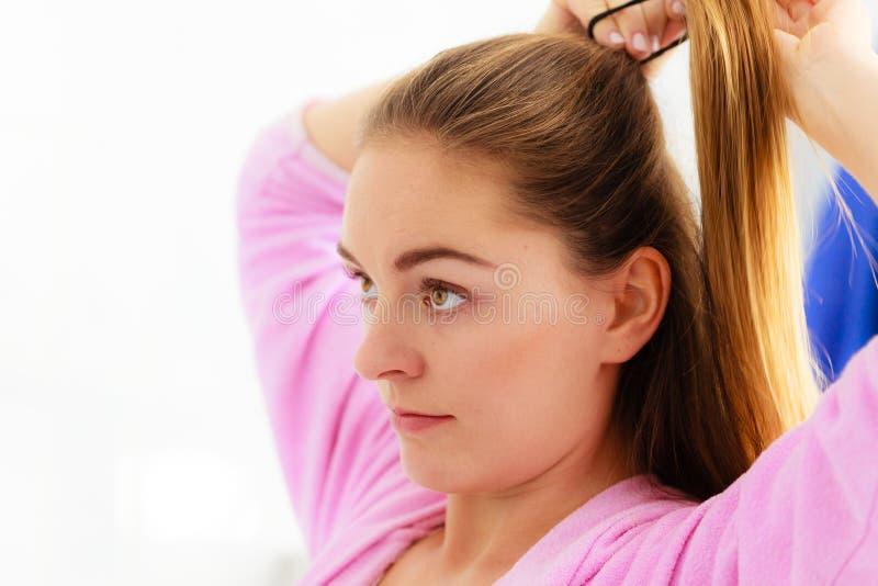 Donna che pettina i suoi capelli lunghi in bagno immagine stock
