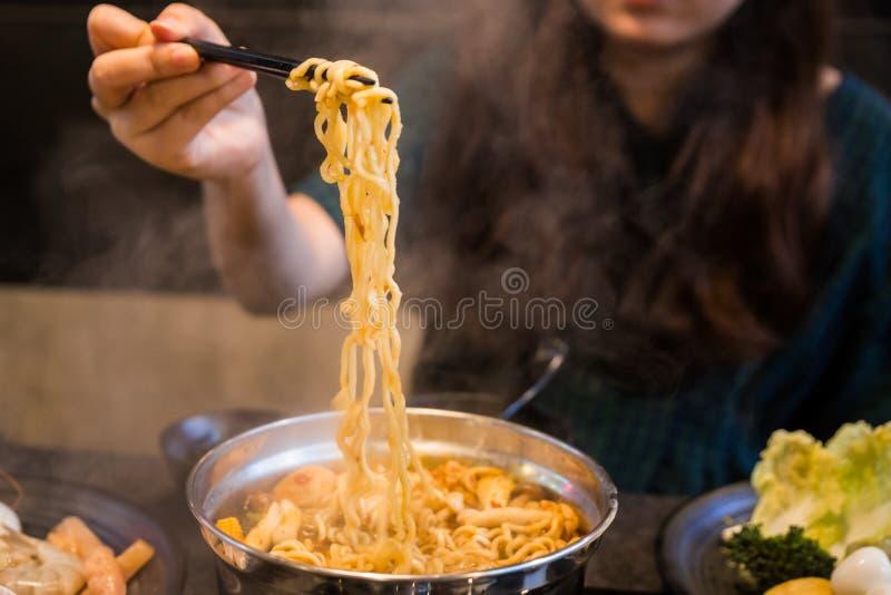 Donna che pizzica tagliatella istantanea coreana bollita nell'aria con i bastoncini dalla cottura a vapore dello stufato di castr fotografia stock libera da diritti