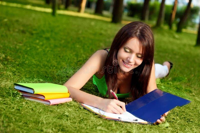 Donna che pone sull'erba e sulla scrittura fotografie stock libere da diritti