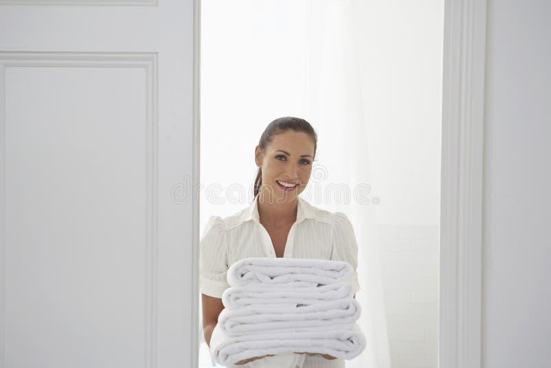 Donna che porta gli asciugamani piegati immagine stock libera da diritti