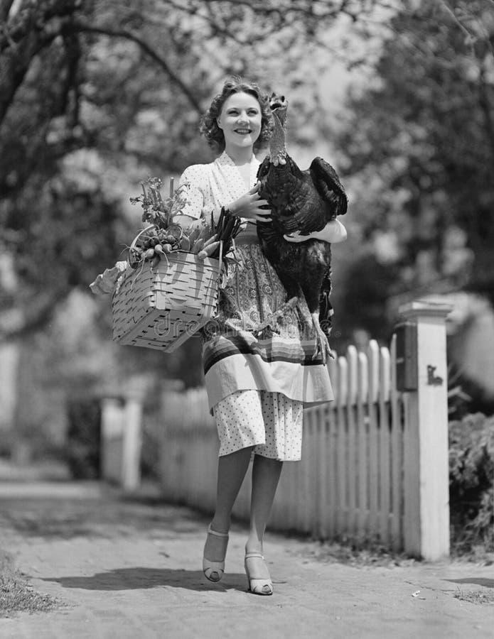 Donna che porta il canestro in tensione della drogheria e del tacchino (tutte le persone rappresentate più lungamente non stanno  fotografie stock libere da diritti