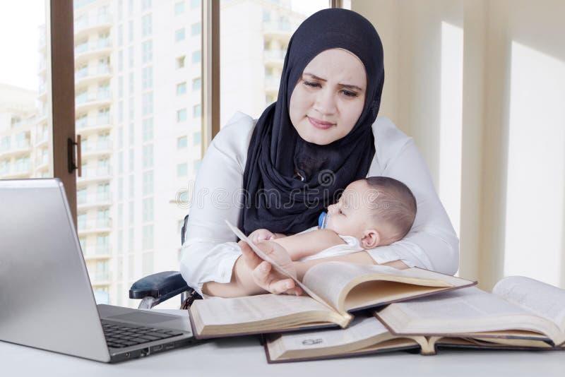 Donna che porta il suo bambino mentre lavorando immagini stock libere da diritti