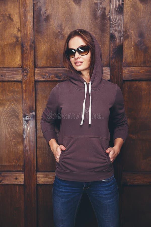 Donna che porta maglietta felpata magenta davanti alla parete di legno immagini stock