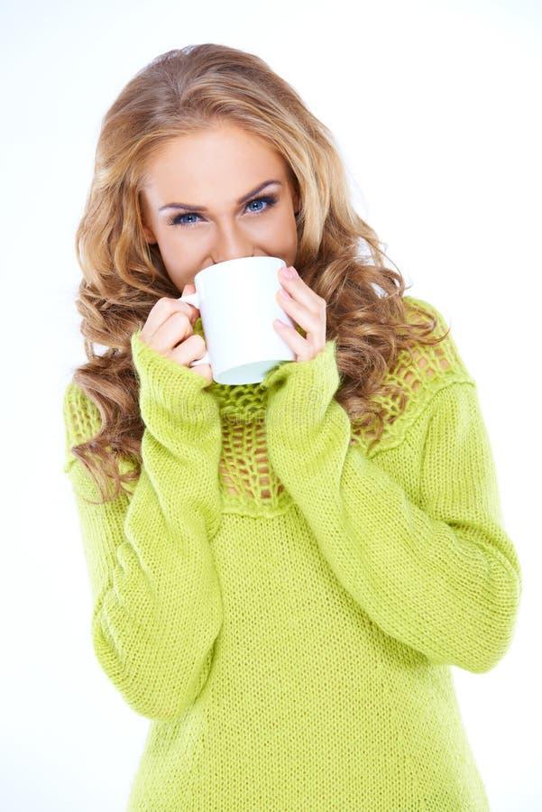 Donna che porta maglione verde che beve dalla tazza fotografia stock libera da diritti