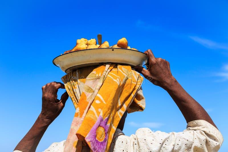 Donna che porta un piatto con alimento sulla sua testa veduta da dietro immagini stock libere da diritti