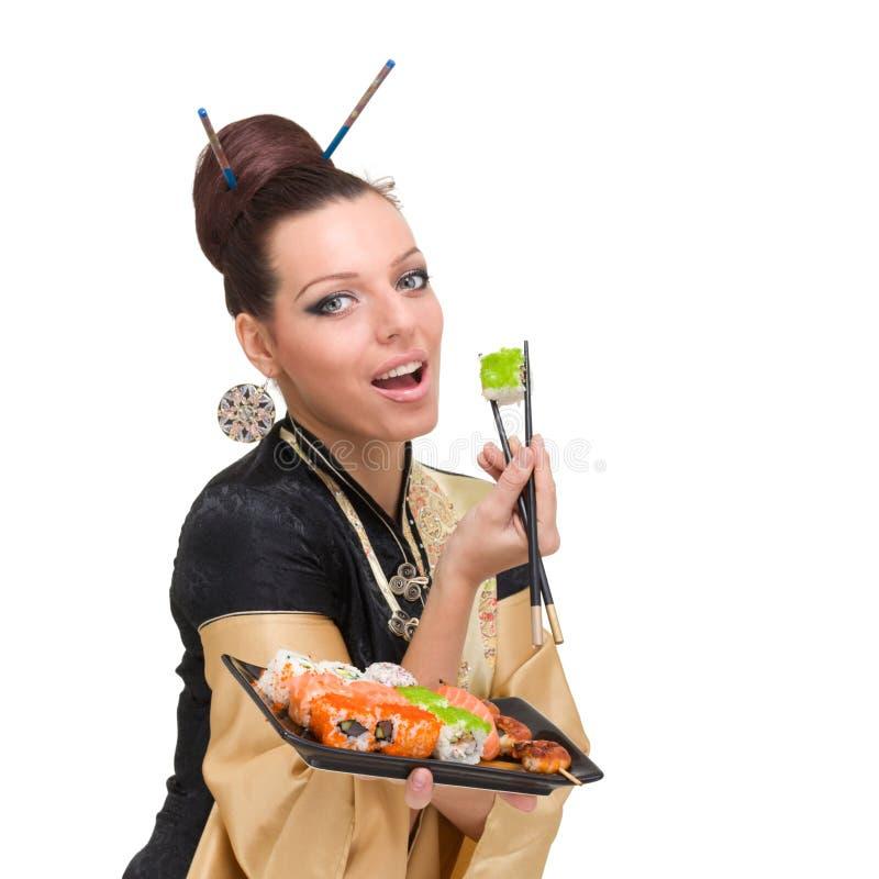 Donna che porta un vestito tradizionale che mangia i sushi immagini stock libere da diritti