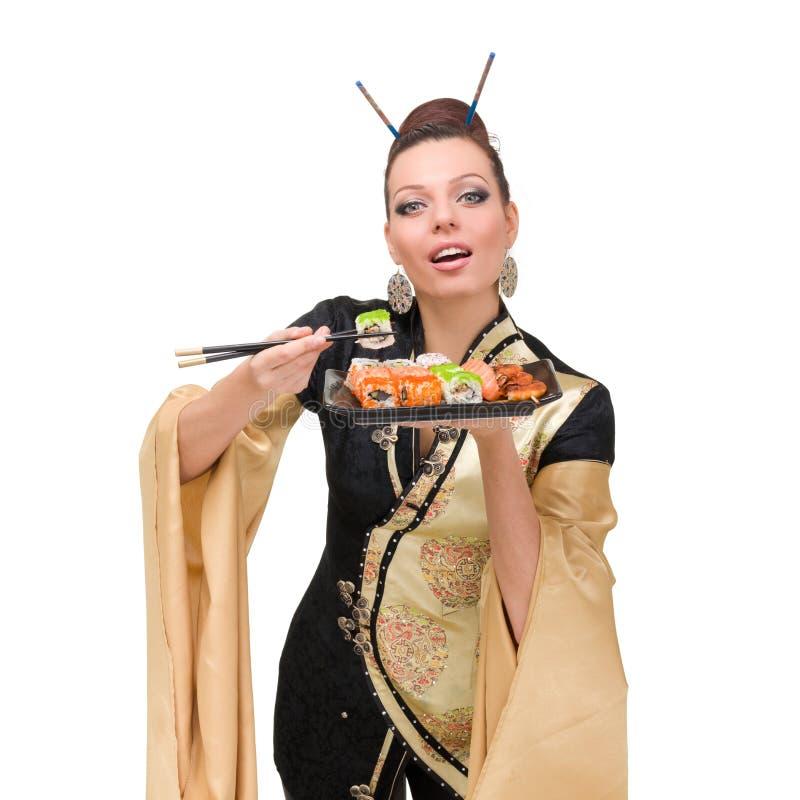 Donna che porta un vestito tradizionale che mangia i sushi fotografia stock libera da diritti