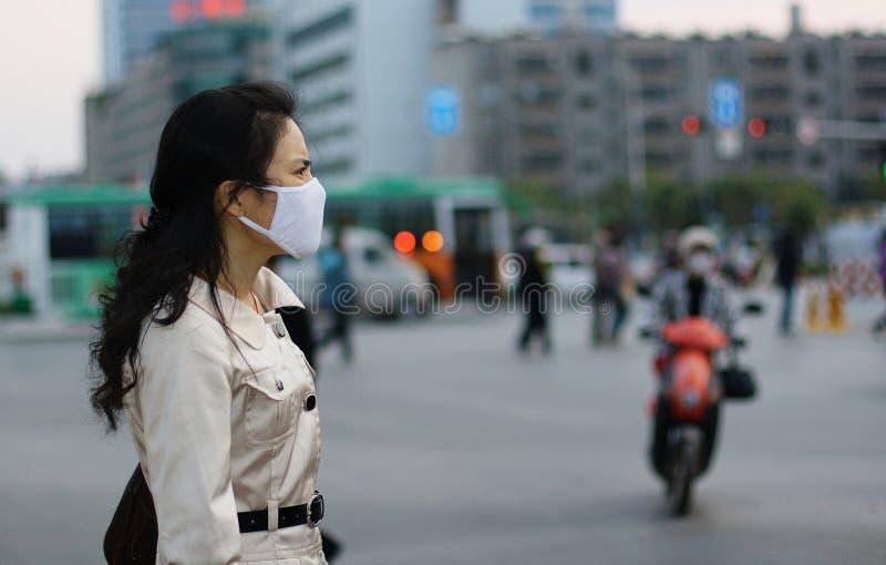 Donna che porta una maschera di protezione fotografia stock