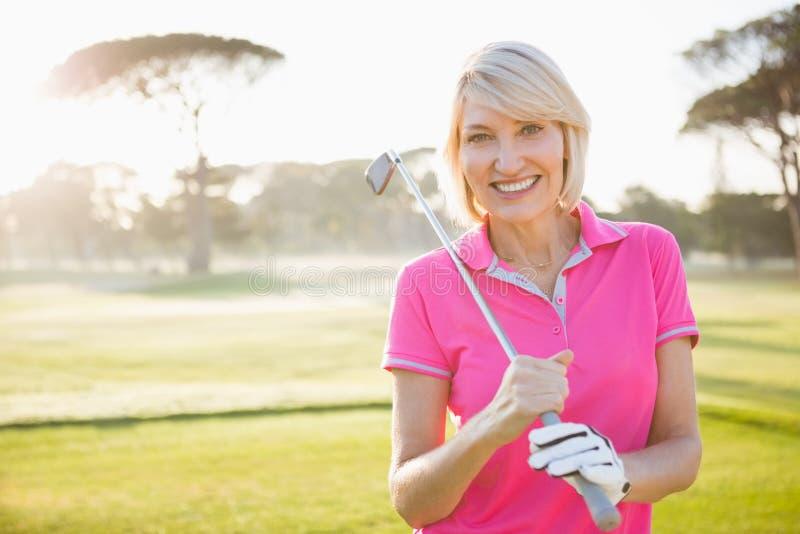 Donna che posa con il suo club di golf immagini stock libere da diritti