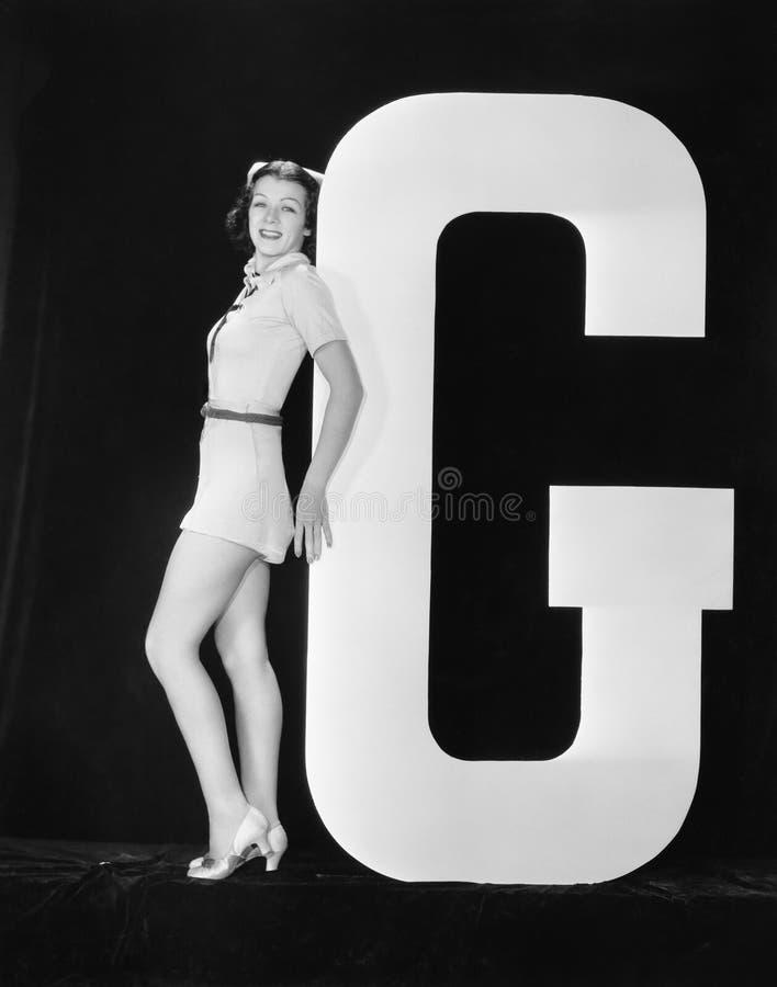 Donna che posa con la lettera enorme G (tutte le persone rappresentate non sono vivente più lungo e nessuna proprietà esiste Gara fotografia stock