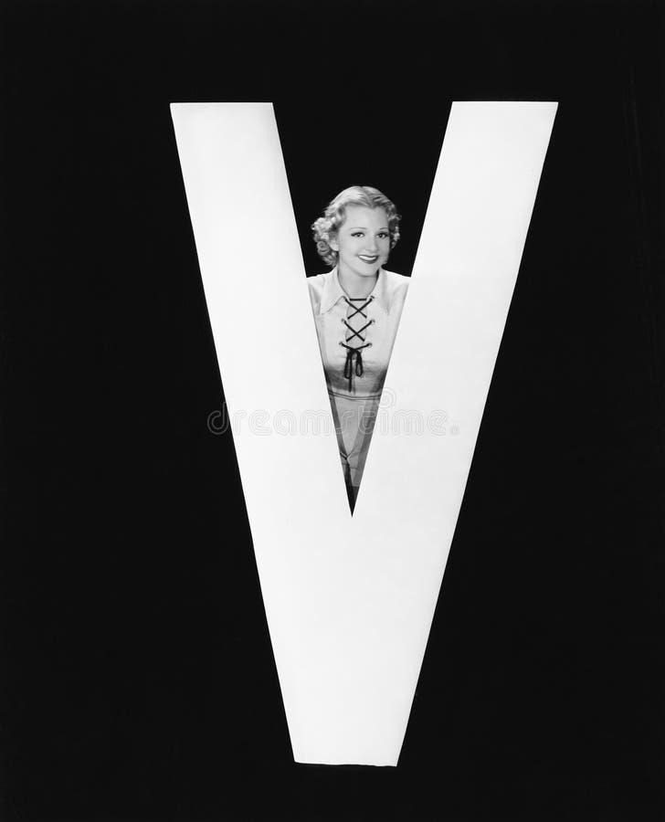 Donna che posa con la lettera enorme V (tutte le persone rappresentate non sono vivente più lungo e nessuna proprietà esiste Gara immagini stock