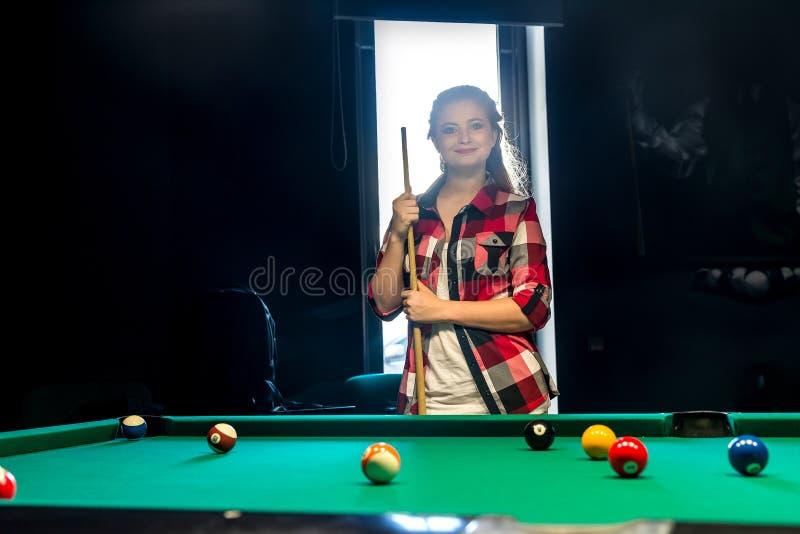 Donna che posa con la stecca nel pub del biliardo immagine stock