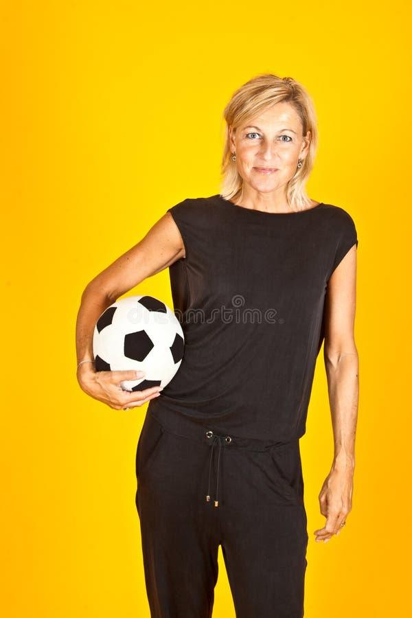Donna che posa con un pallone da calcio immagini stock libere da diritti