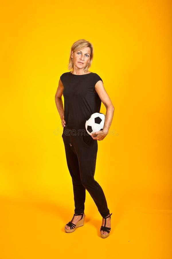 Donna che posa con un pallone da calcio immagini stock