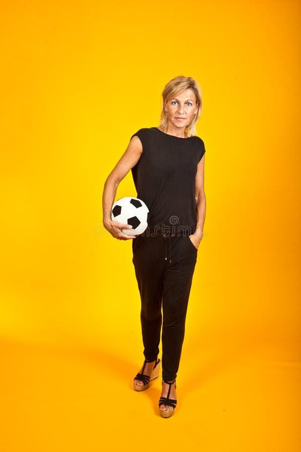 Donna che posa con un pallone da calcio fotografia stock