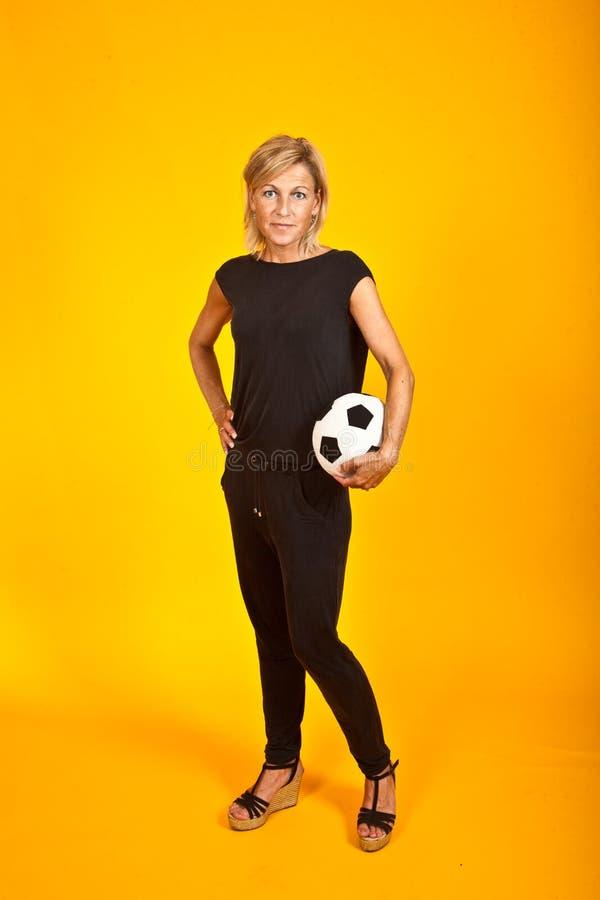 Donna che posa con un pallone da calcio immagine stock