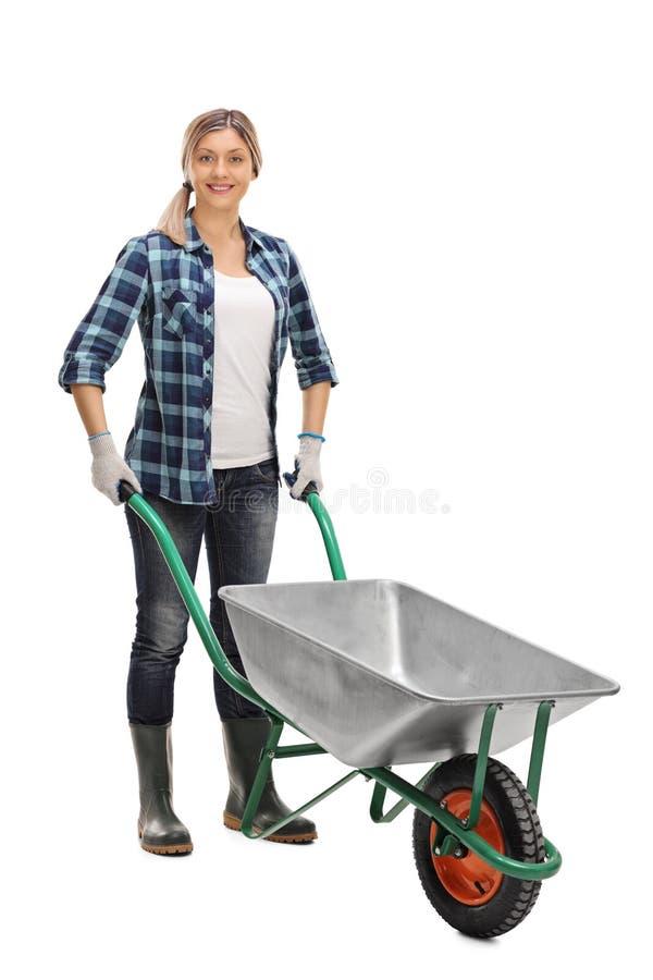 Donna che posa con una carriola vuota fotografia stock libera da diritti