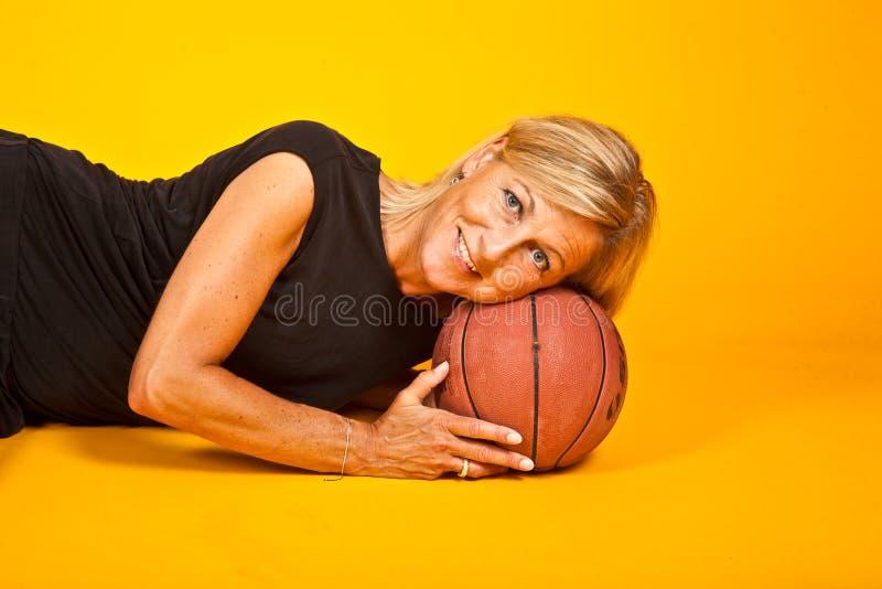 Donna che posa con una palla del canestro fotografie stock libere da diritti