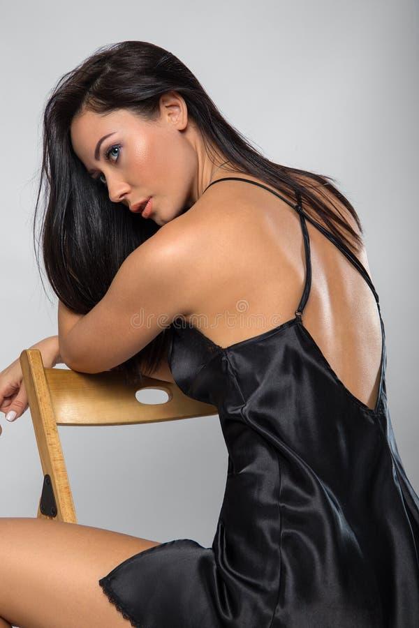 Donna che posa nella biancheria nera con la sedia immagini stock