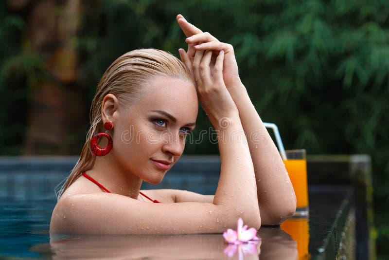 Donna che posa nella piscina tropicale immagini stock libere da diritti