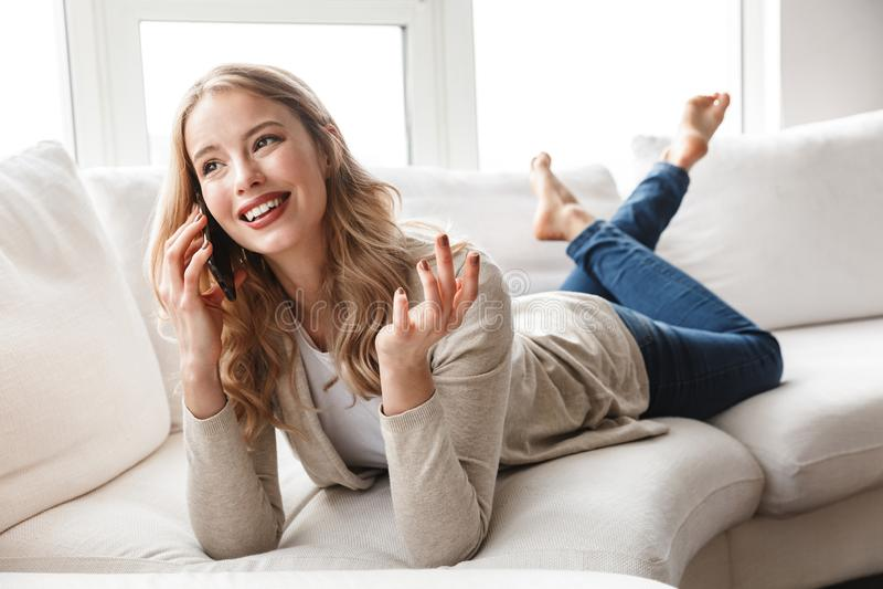 Donna che posa seduta all'interno a casa che parla dal telefono cellulare fotografia stock libera da diritti