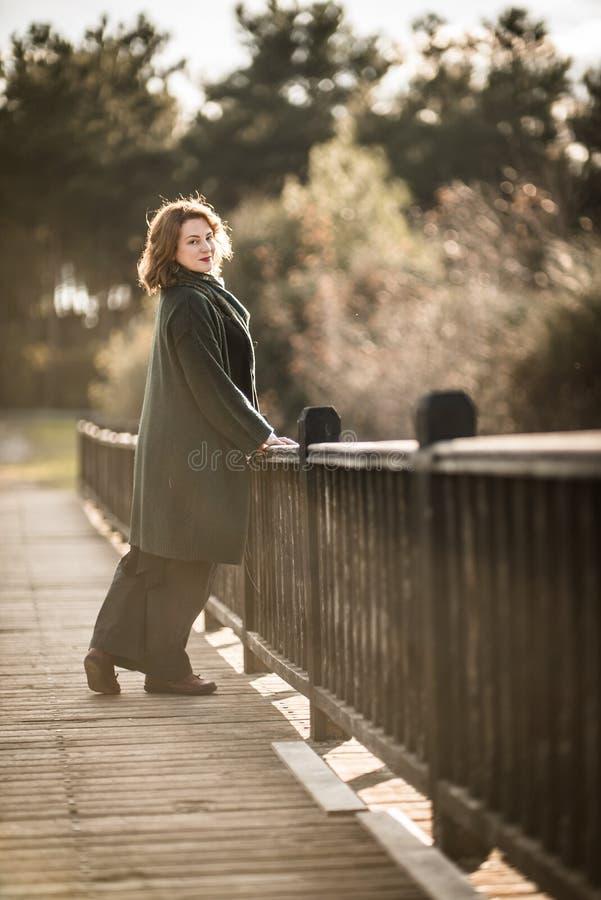 Donna che posa su un vecchio ponte di legno immagini stock libere da diritti