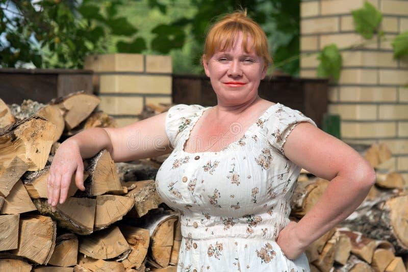 Donna che posa sui precedenti di legna da ardere fotografie stock libere da diritti